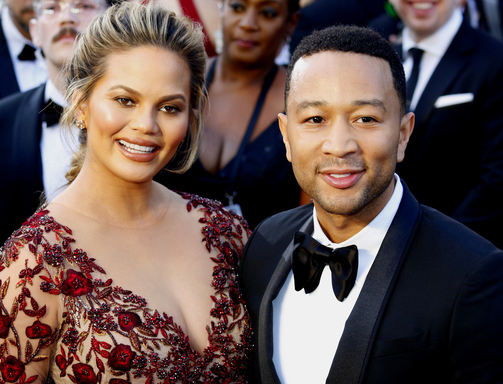 Chrissy Teigen and John Legend standing together at an event in formal wear.