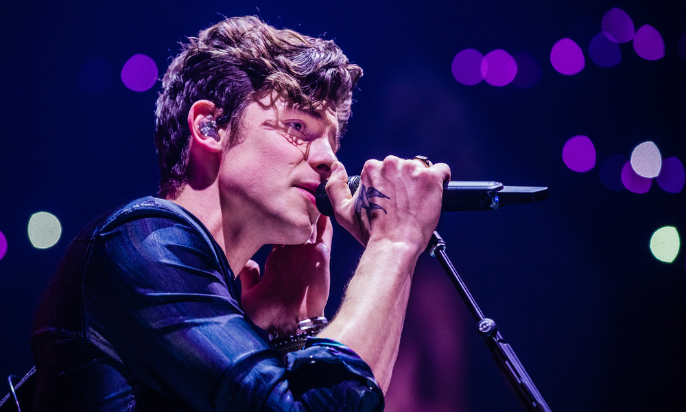 Shawn Mendes singing into a microphone during a live performance.